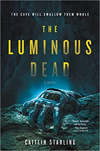 Cover of The Luminous Dead, which features a hand wearing the glove from a high-tech space suit