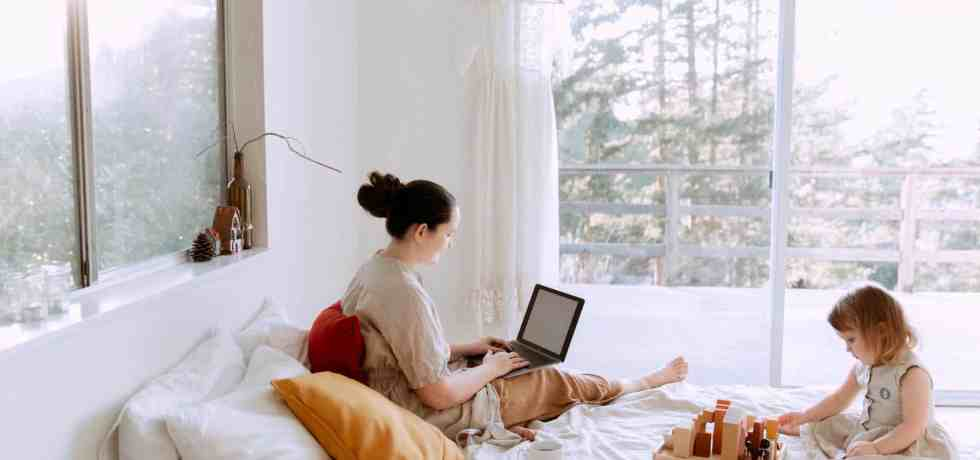 adorable toddler girl playing with wooden blocks sitting on bed while mother using laptop on sunny morning