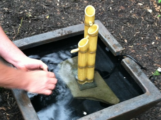 Set up of bamboo fountain, using a flat piece of stone to raise it up slightly