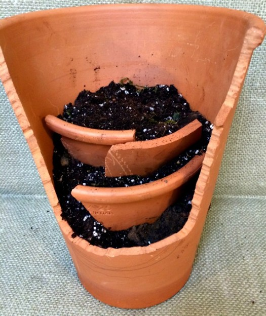 Add potting soil and insert your slabs of terra cotta