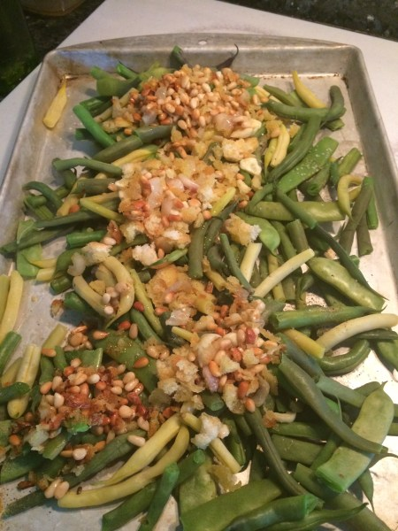 the cookie sheet with green beans, garlic, olive oil, pine nuts, breadcrumbs and cheese