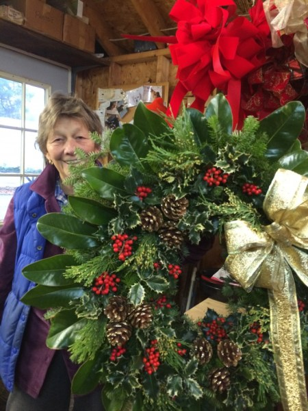 Miriam, chief elf at McLean, displays one of her creations, accented with Magnolia leaves