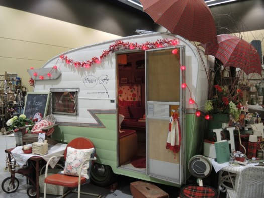 An old trailer that displays vintage gardening equipment at the Northwest Flower and Gardening Show