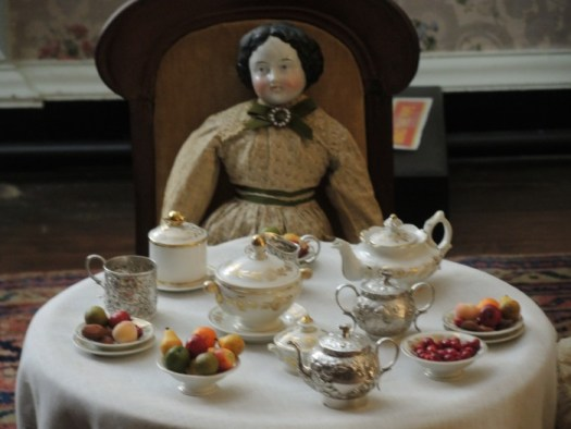 Doll with tea set in one of the bedrooms