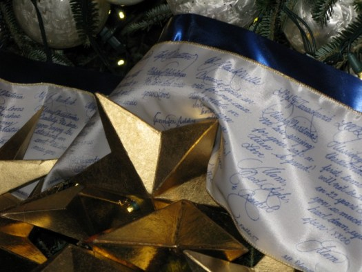 Silk ribbon garland inscribed by a calligrapher with messages from military families on the Blue Room tree