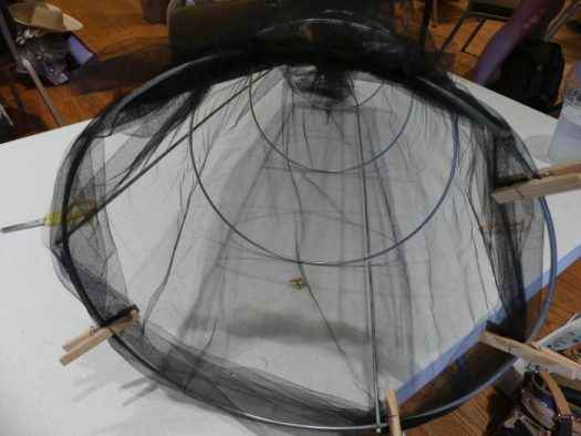 Using clothes pins to fasten the bottom of the tulle, use needle and thread to overcast stitch the tulle firmly to the bottom ring