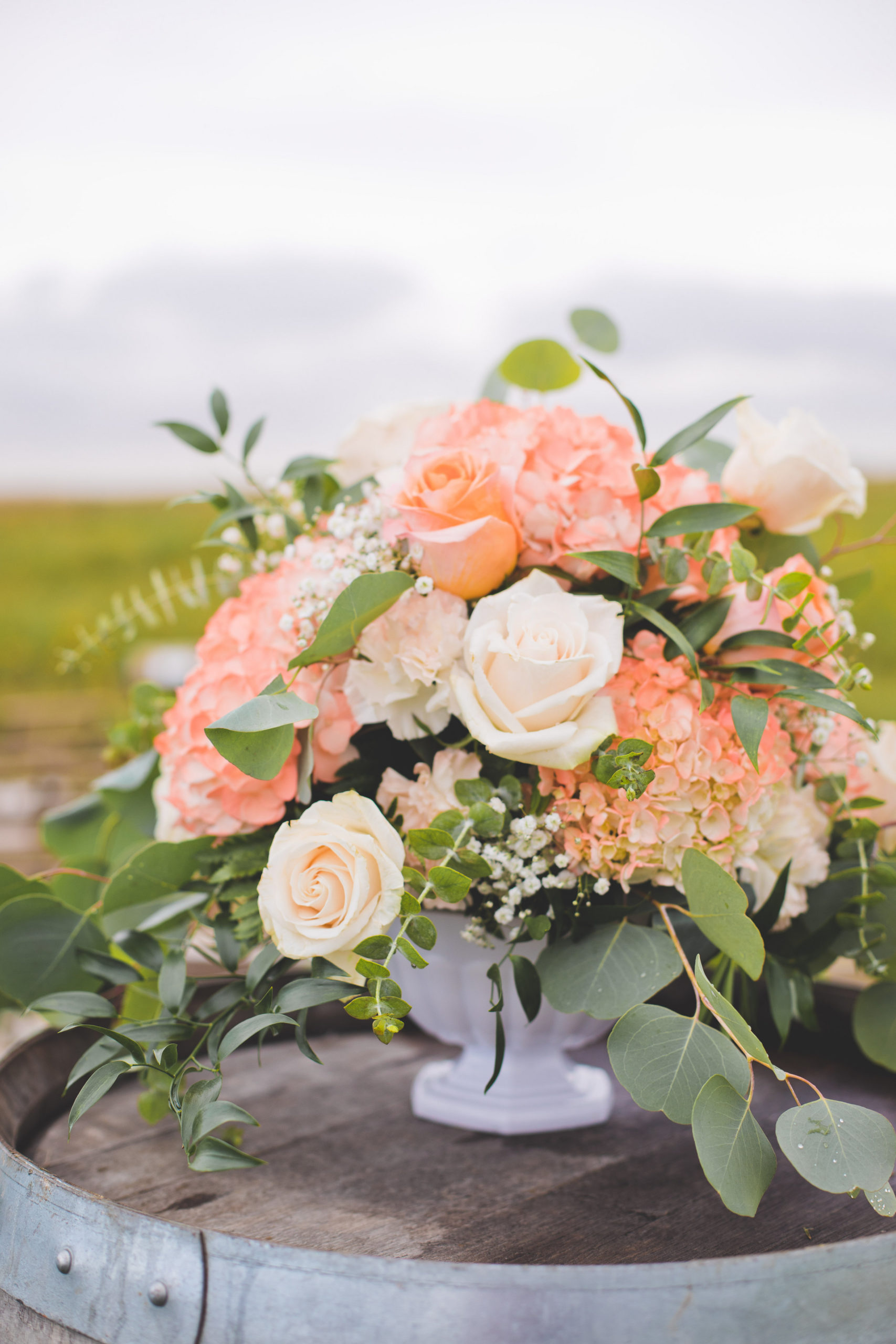 Beautiful pink, coral and peach hydrangeas and roses placed on a wine barrel in a prairie field. A vibrant wedding at the Gathered.