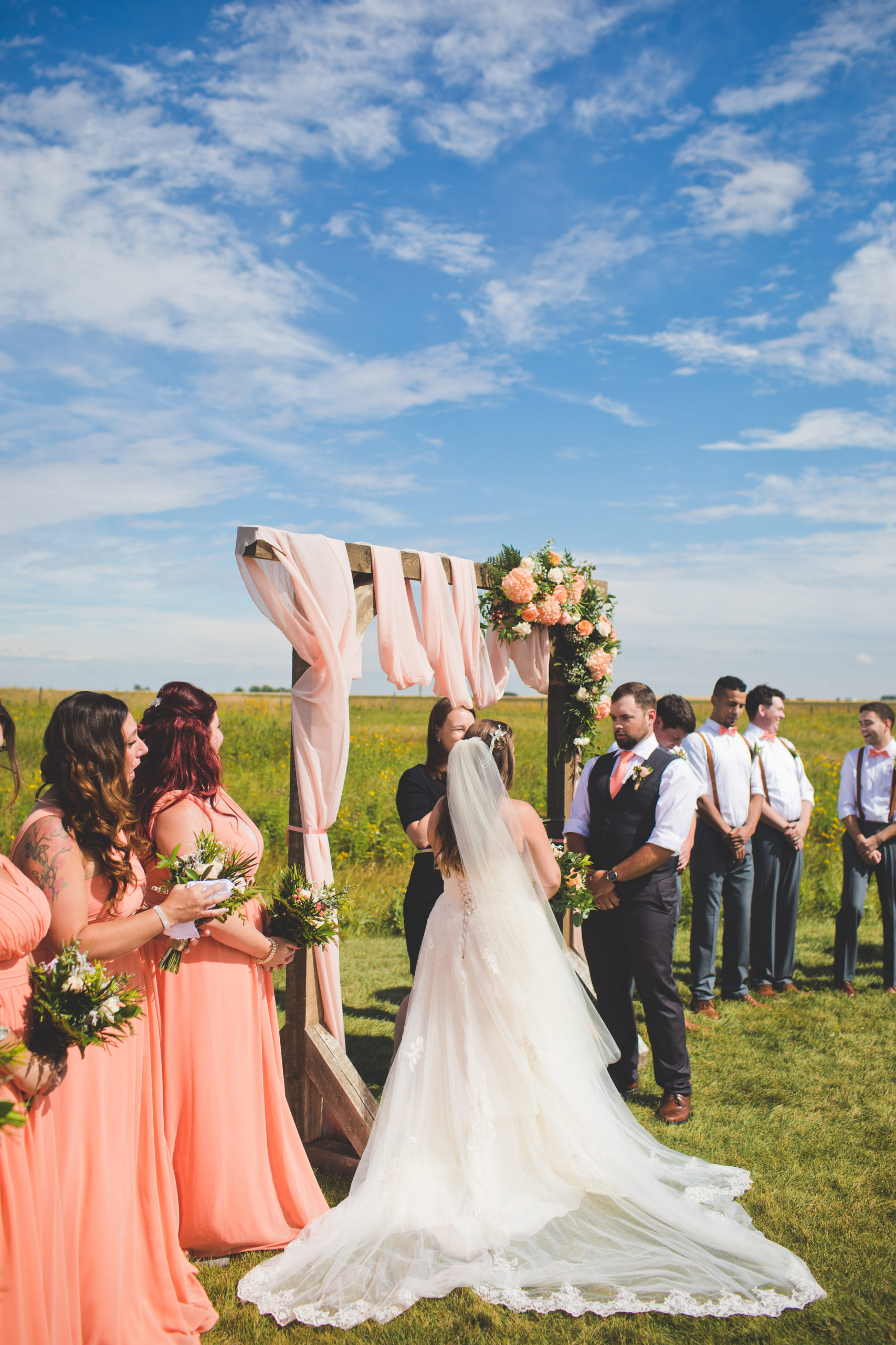 couple standing at the alter of their outdoor wedding in a prairie field with bright blue skies. Bridal party looking spiffy in vibrant coral dresses and coral bow ties.
