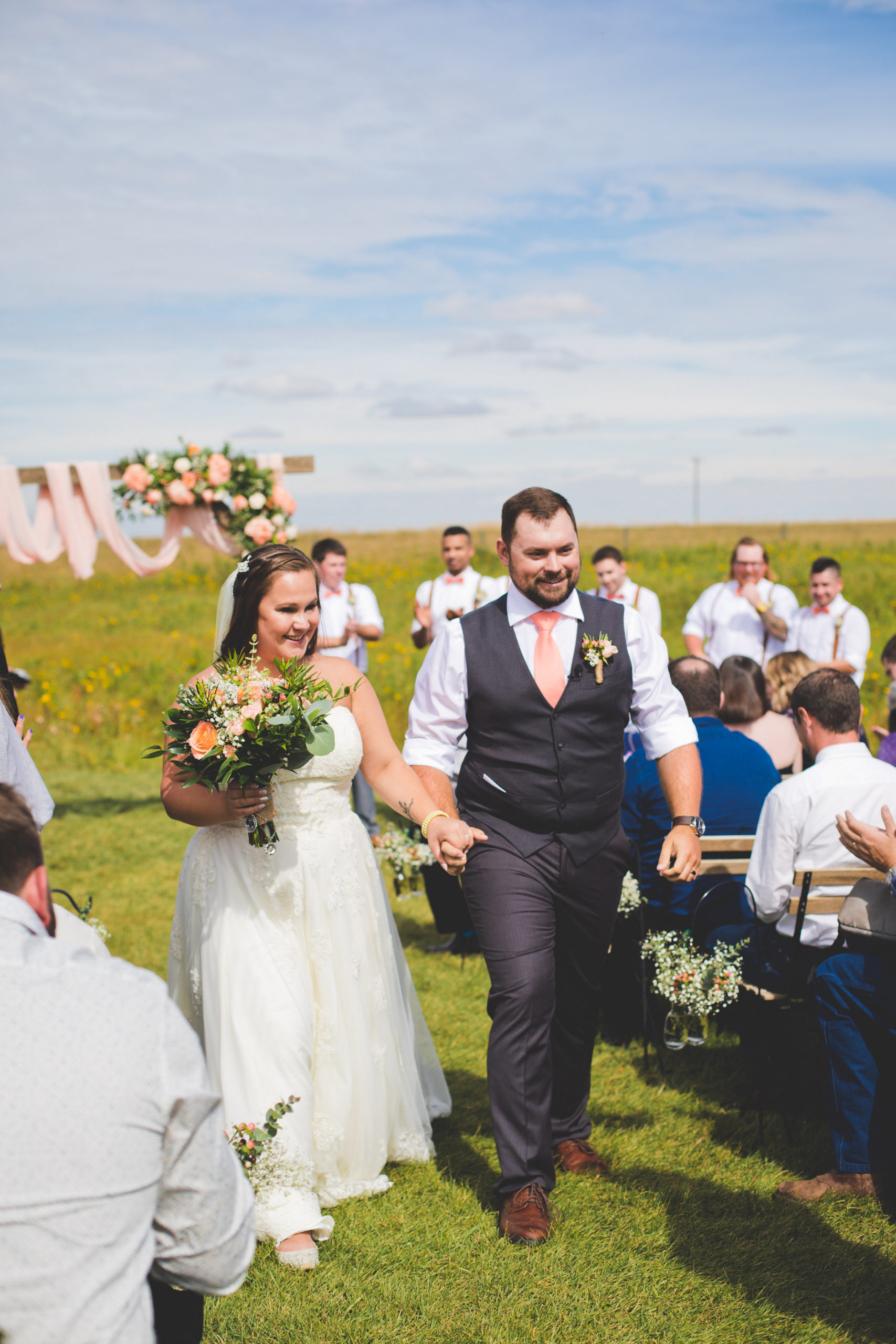 walking down the aisle just married surrounded by prairie fields and pink and coral tones in the decor.