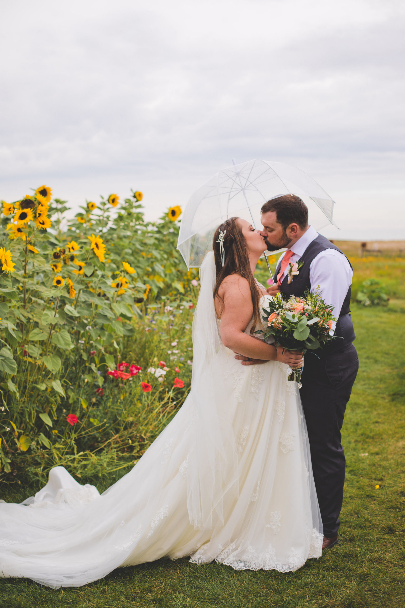 sunflowers and wildflowers make this garden and wedding space magical. The brides white lacy dress contrasts the wildflowers on this rainy Alberta prairie day. The Gathered.