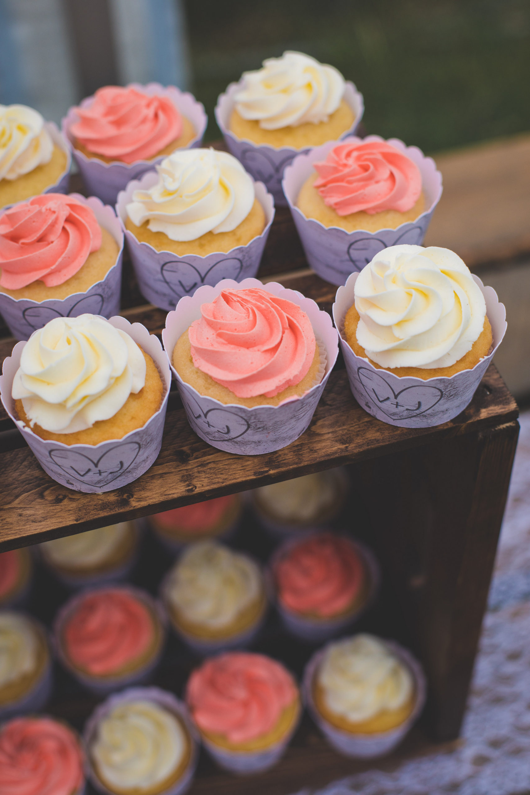 cupcakes decorated with white icing and coral icing - cupcakes are stacked on a wood crate.