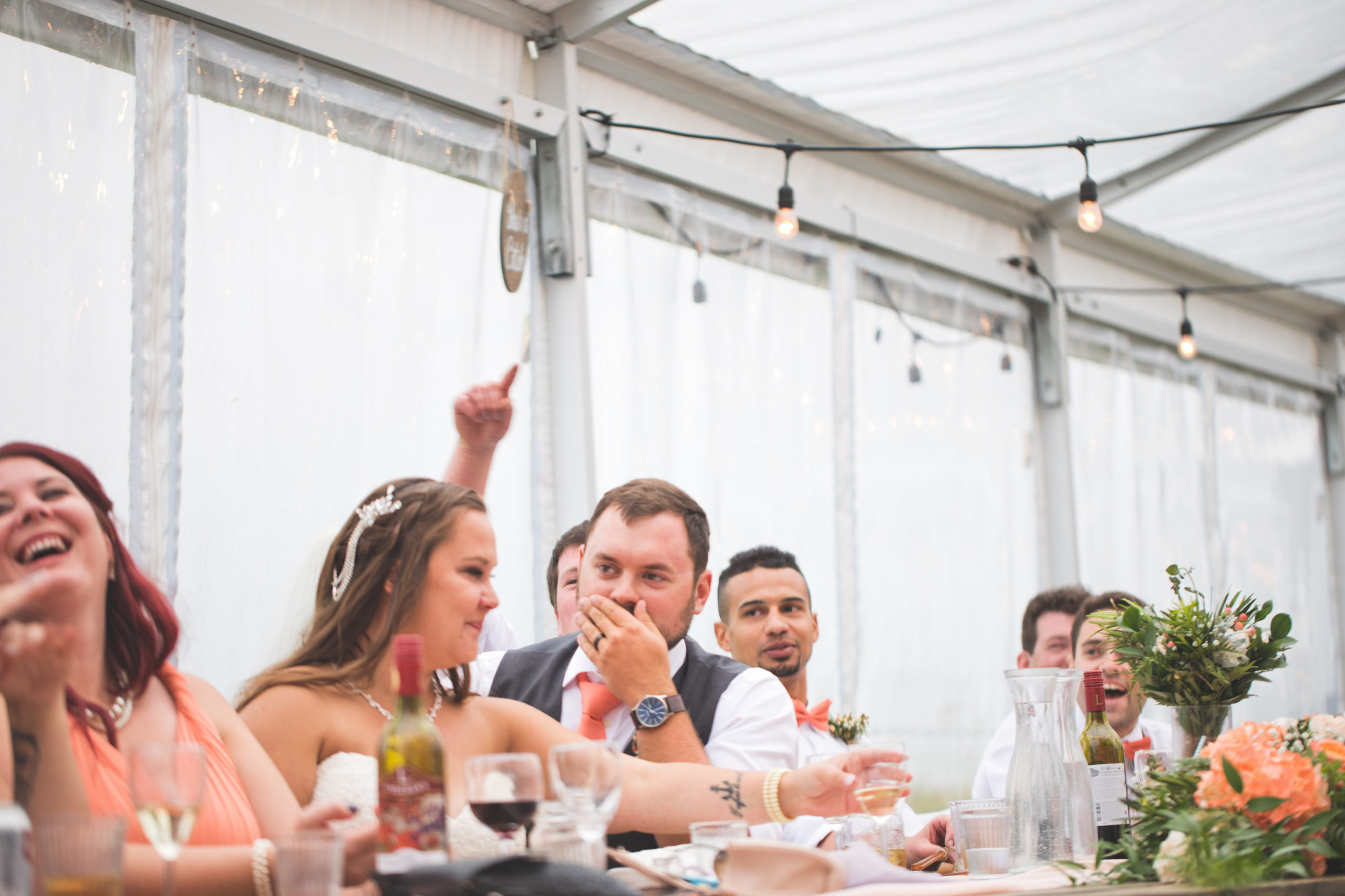 wedding party at reception laughs as speeches are made. Vibrant coral decor brightens up this outdoor clear tent.