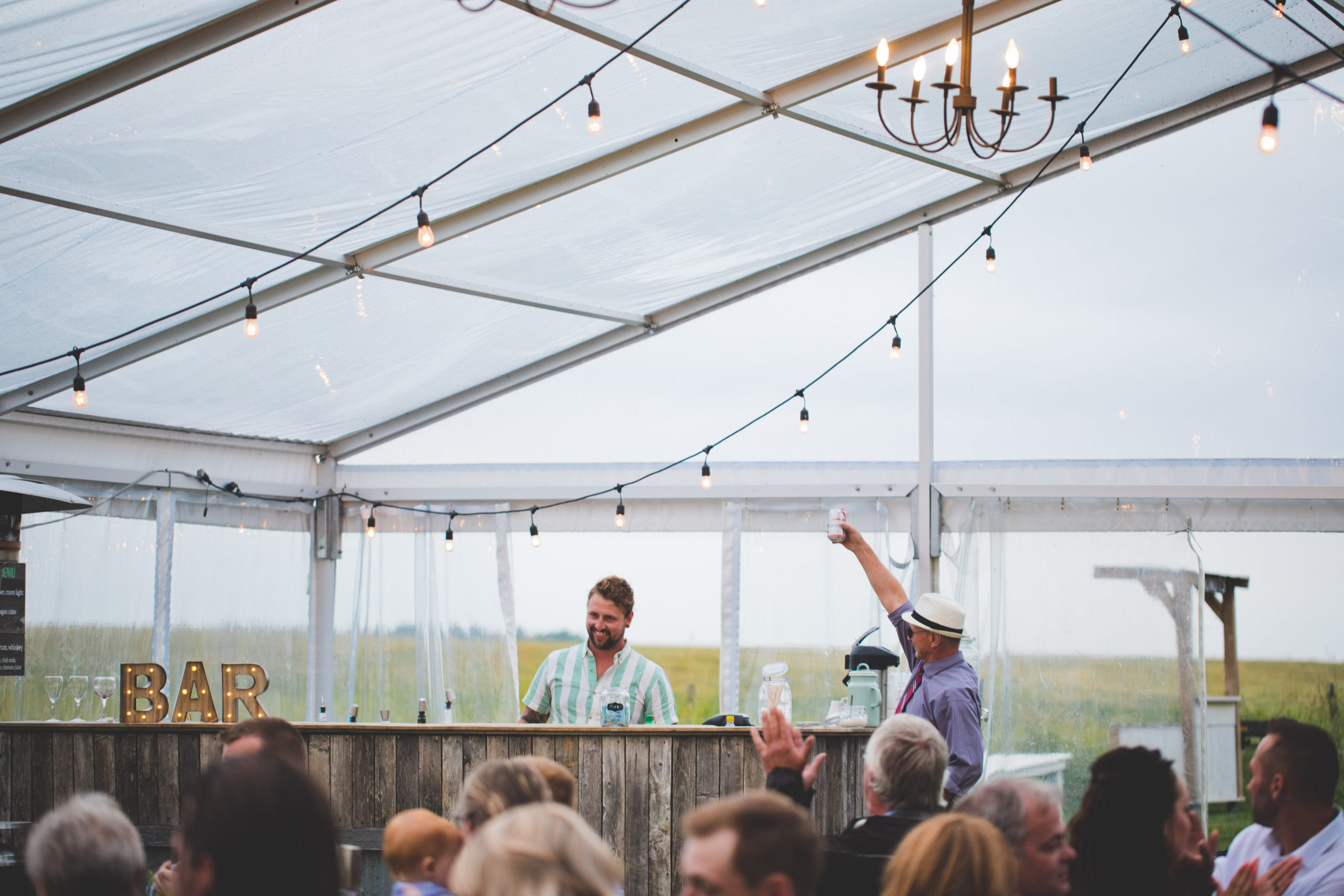 in a clear tent with hanging globe lights wedding guess salute the bartender at this outdoor wedding in the rain.