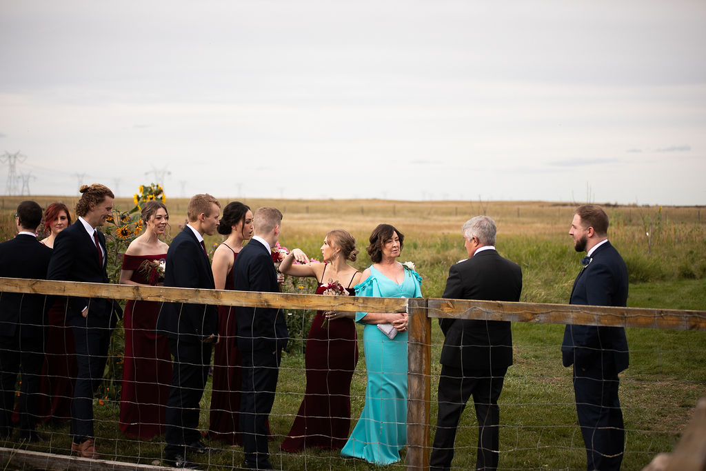 the family waits to walk down the aisle at this outdoor farm wedding, the bridesmaids in burgundy dresses and mother of the bride in bright blue.