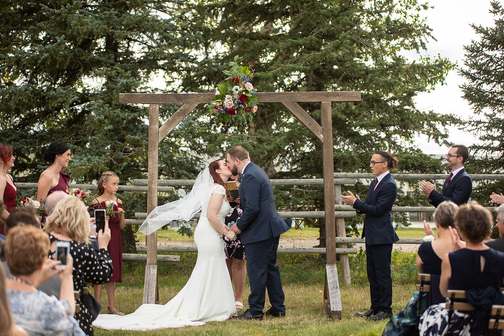 just married kiss under a wooden arbor at this outdoor ceremony space - surrounded by big green trees and loving guests .