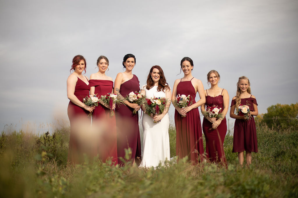 6 bridesmaids in burgundy floor length dresses surround a bride while standing in a prairie field. www.thegathered.ca