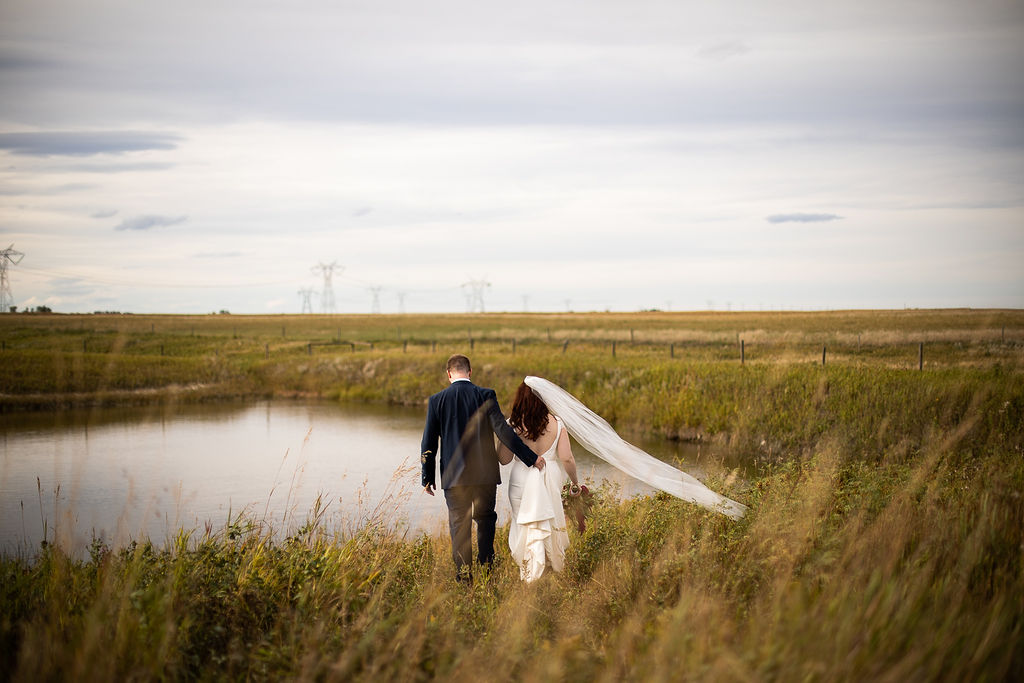 prairie fields surround a pond of water, a couple walks towards the water while the groom helps the bride with her wedding dress train. www.thegathered.ca