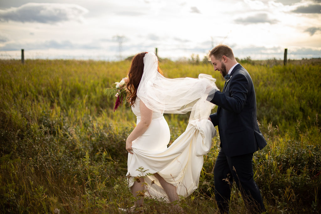 a couple walks through wild prairie fields - the groom helps the bride with her long dress train and her veil. the sun sets in the back. www.thegathered.ca