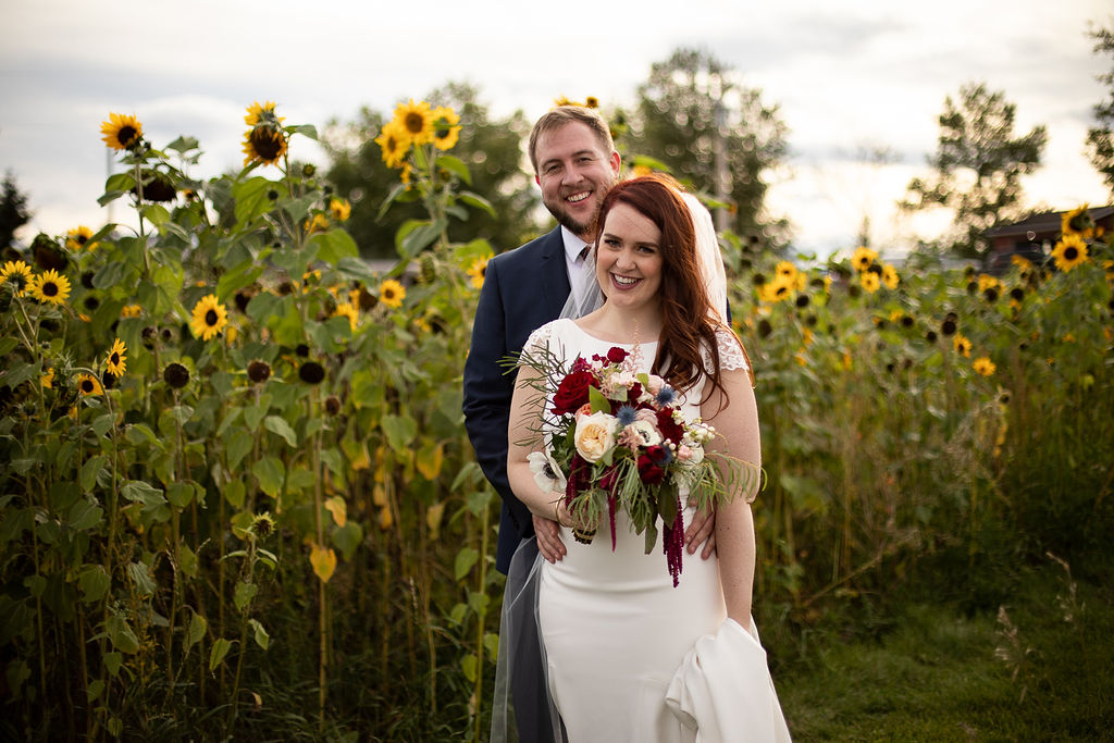 a bride and groom stand beside a row of bright yellow sunflowers at their outdoor wedding in southern Alberta. www.thegathered.ca