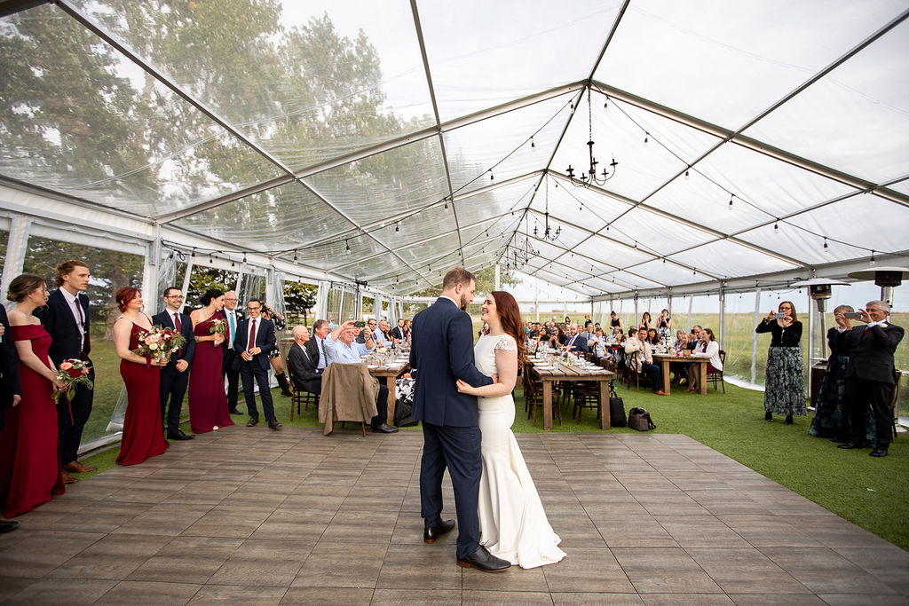 First dance in a clear tent, weddings guests watch from their tables as the couple dances under the open sky at this outdoor wedding. The Gathered, Calgary Alberta