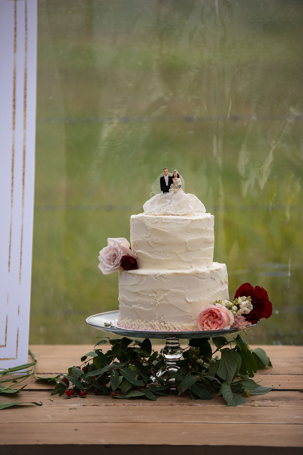 vanilla wedding cake with burgundy and pink flowers.