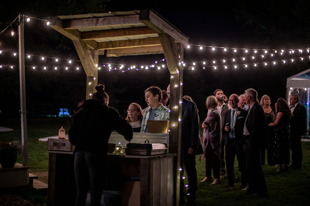 wedding guests line up at the donut stand while globe lights hang overtop. www.thegathered.ca