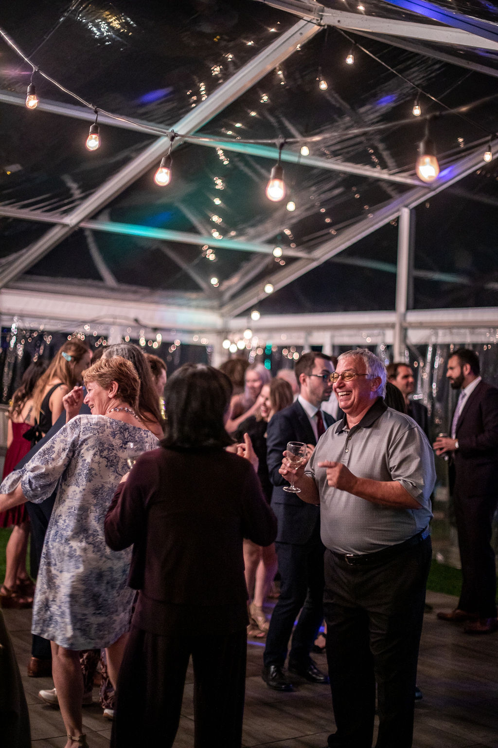 guests mingle on the dance floor of this outdoor wedding venue.