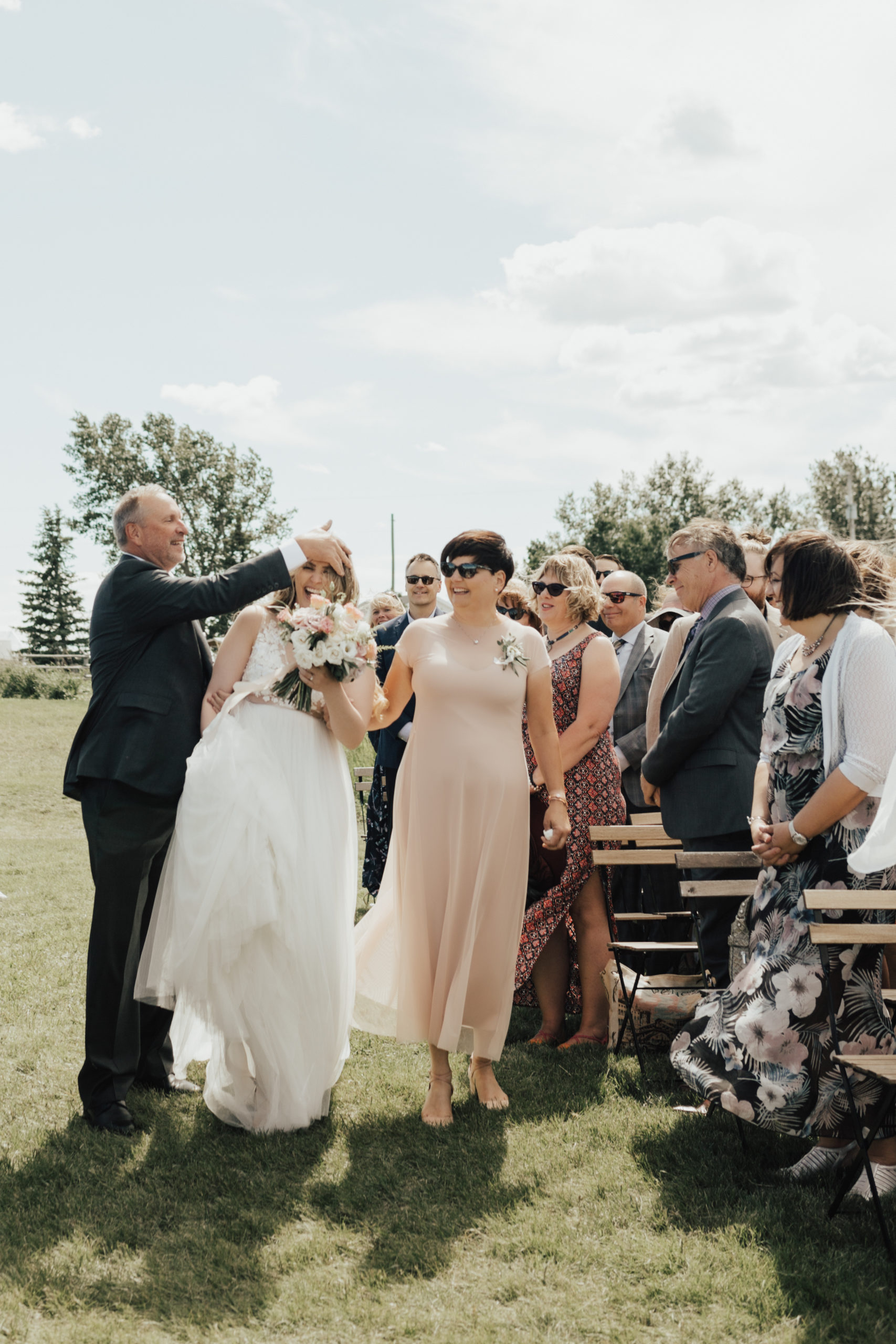 father of the bride fixes brides hair that is in her face as she is walking down the aisle of her modern outdoor wedding venue.