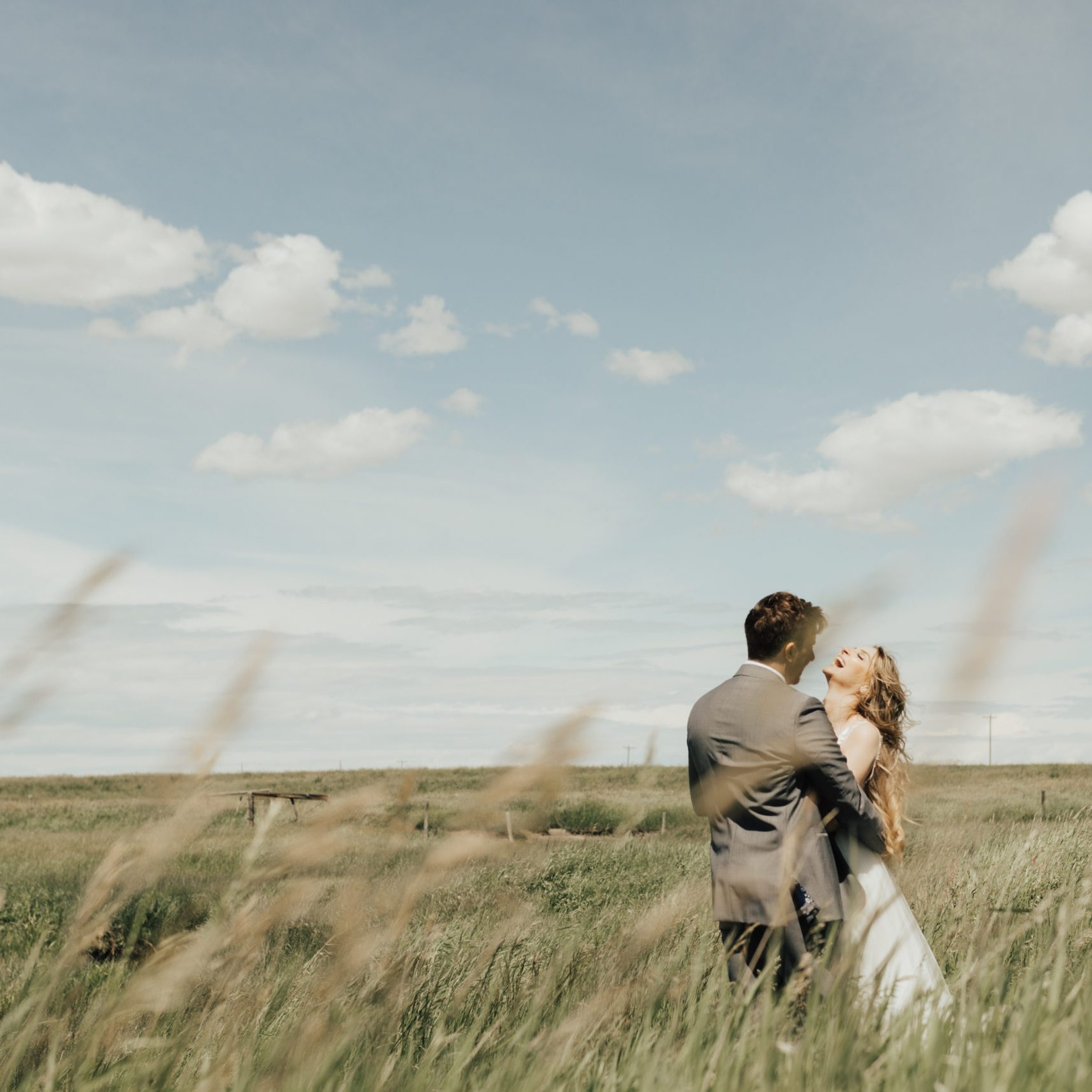 bride laughs in a prairie field while groom puts his arms around her at their outdoor modern wedding. www.thegathered.ca