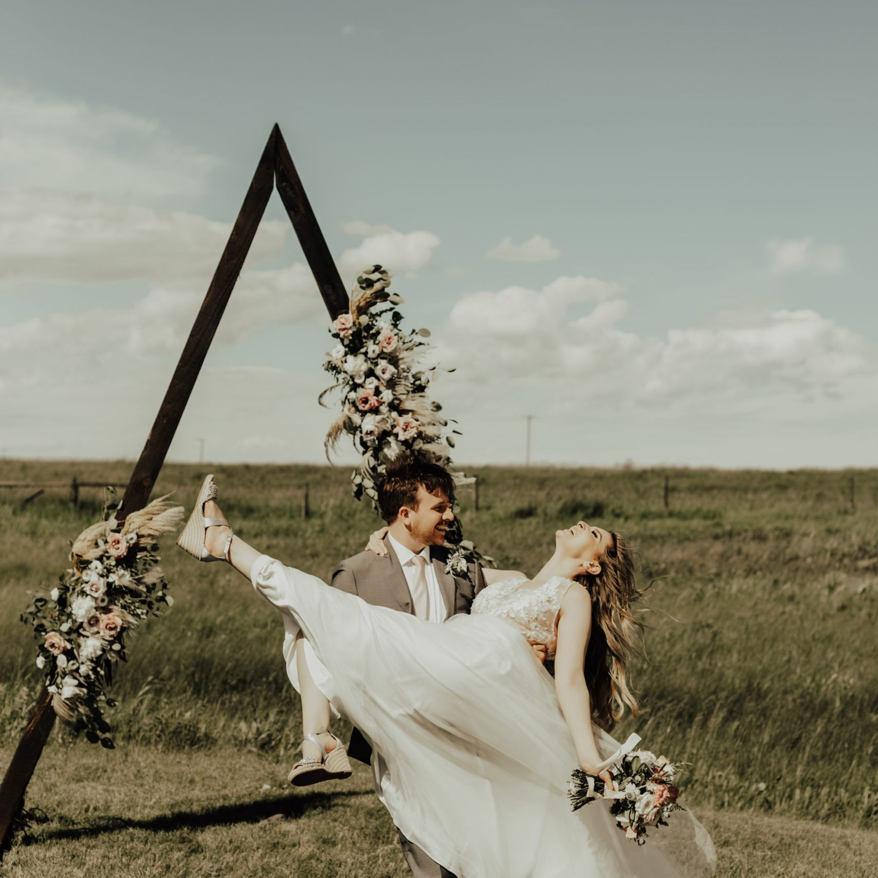 groom lifts the bride while her modern dress blows in the wind, a triangle arbor decorated with romantic flowers make the backdrop while in a prairie field. www.thegathered.ca