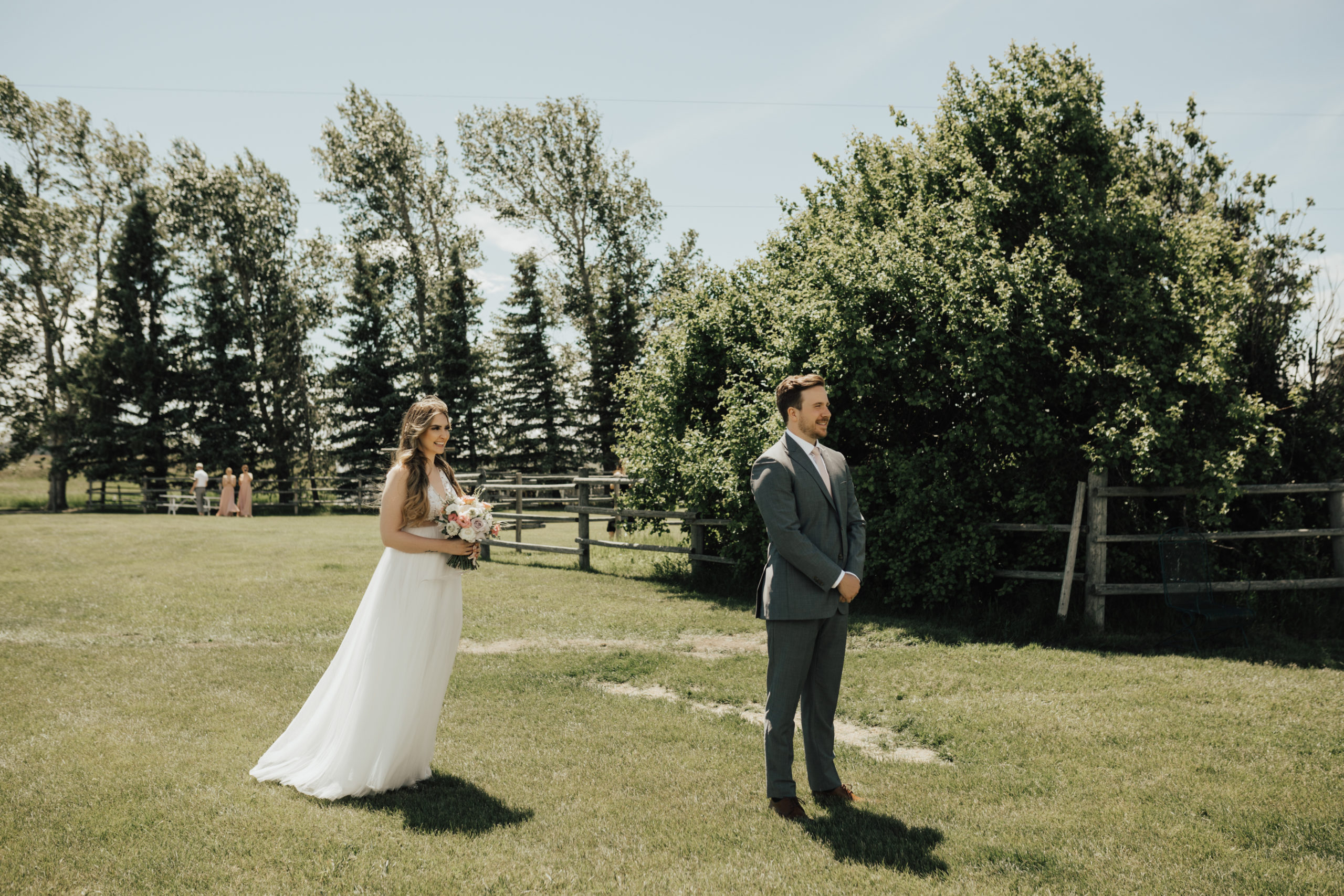 groom waits for his bride as she walks up to him for their wedding first look