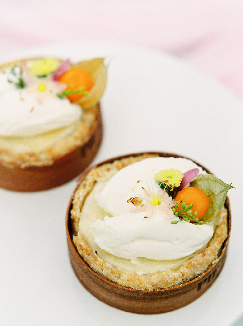 two mini pies with white whipped cream and a floral topper