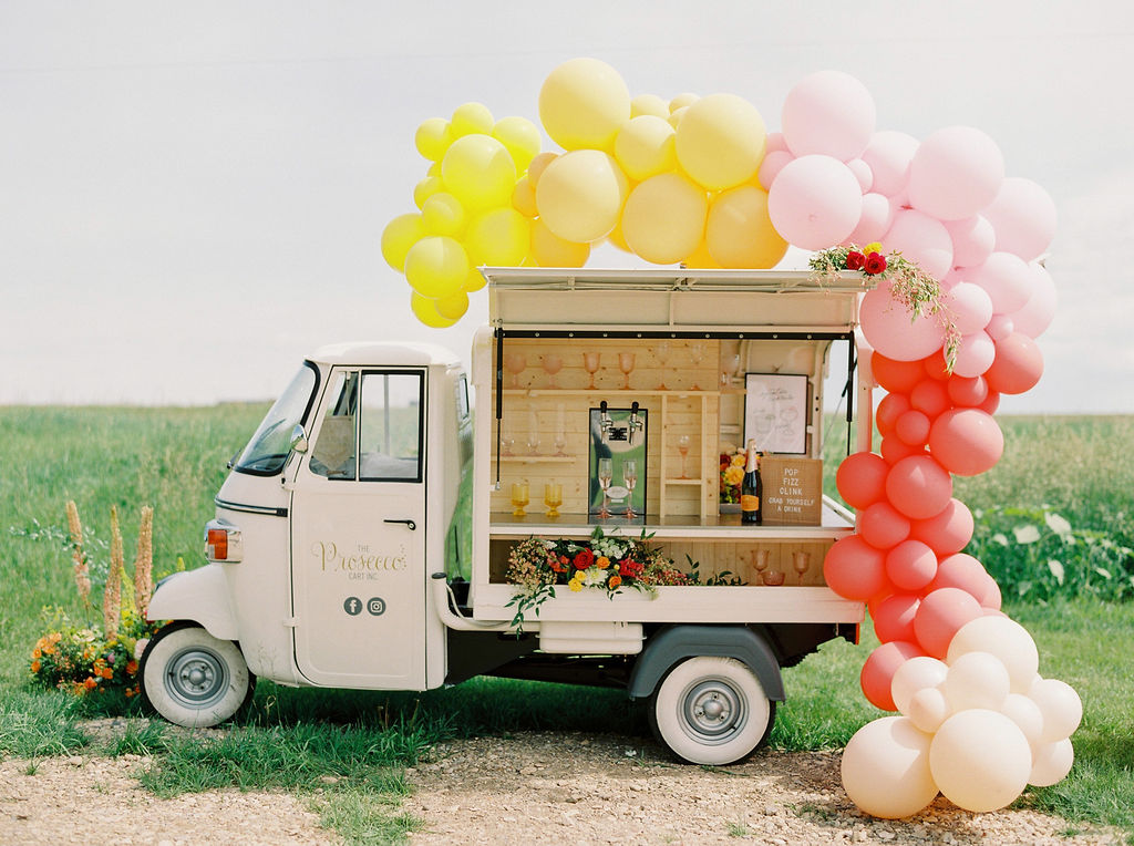 yellow, pink and red balloons surround a small Prosecco cart while parked in a bright green spring field