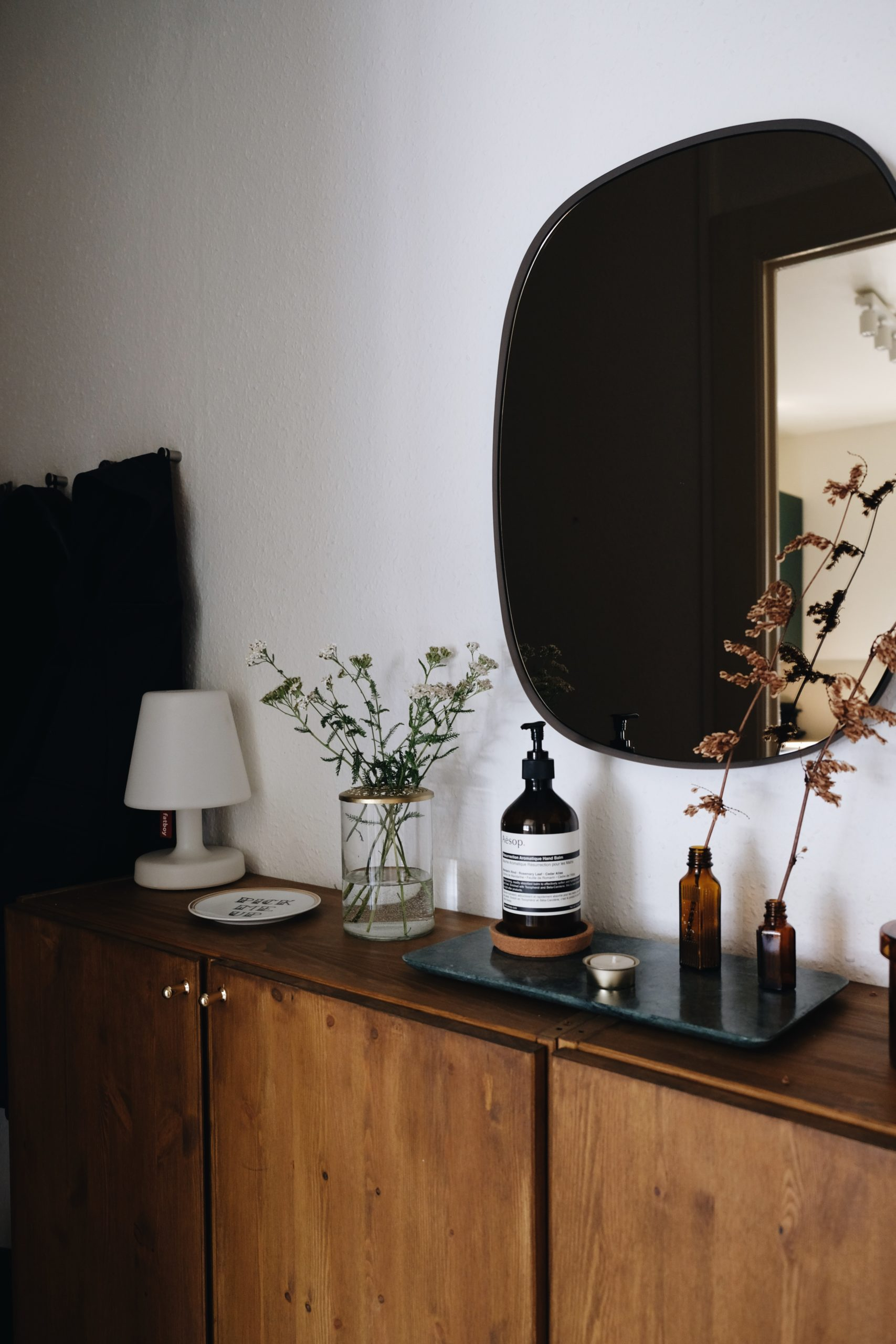 entryway mirror with cupboard and rounded rectangular mirror