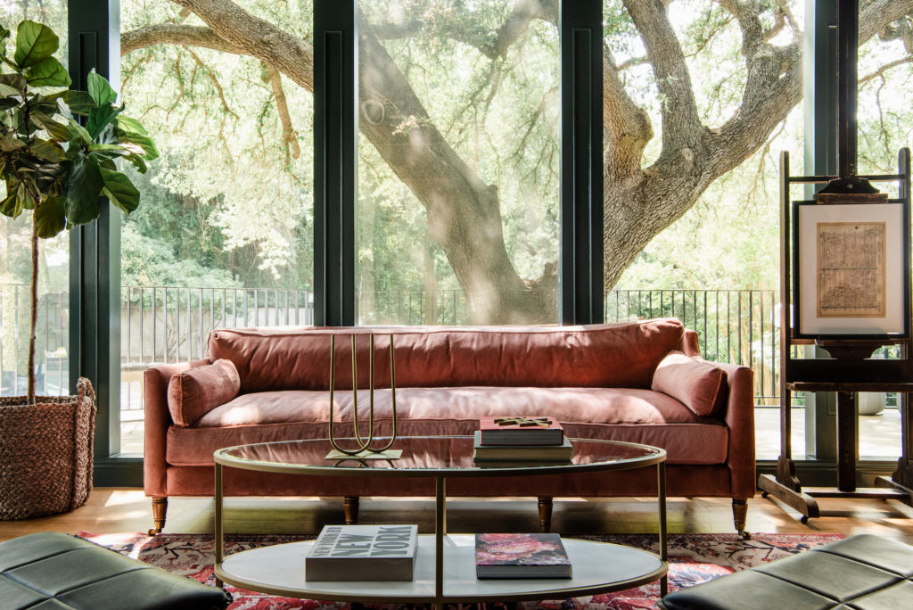 pink velvet sofa with antique easel and modern coffee table