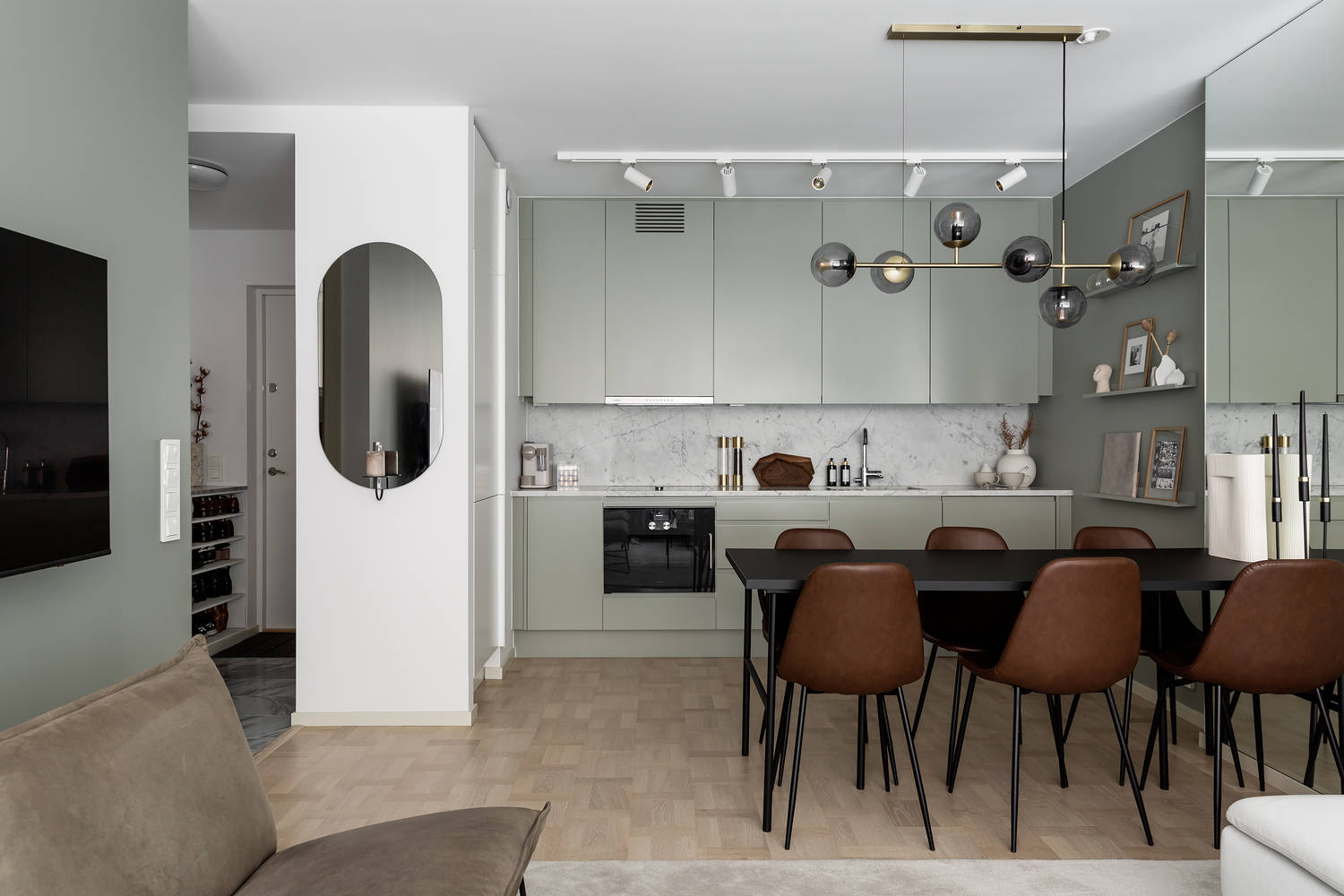 open plan living area with sage green walls kitchen + dining room