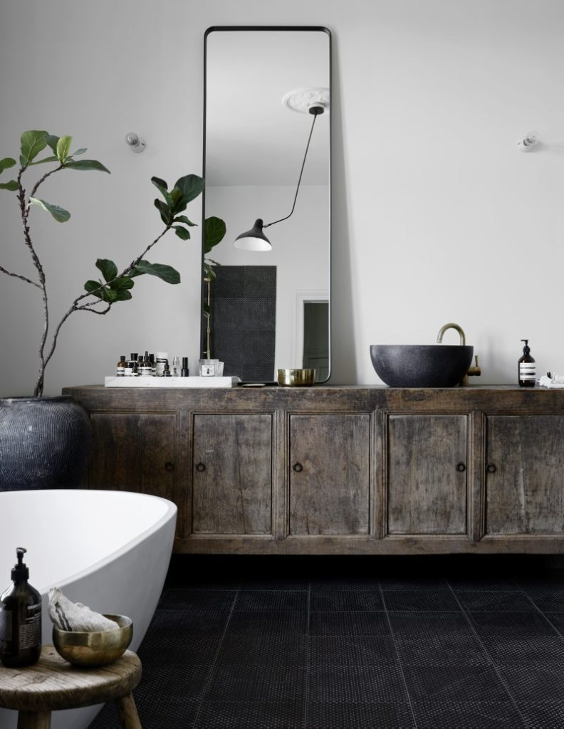 black and white bathroom with vintage sideboard