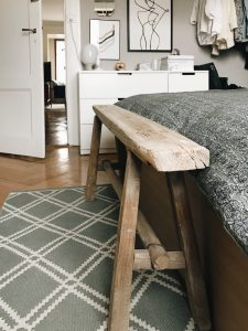 antique wooden bench at the end of the bed