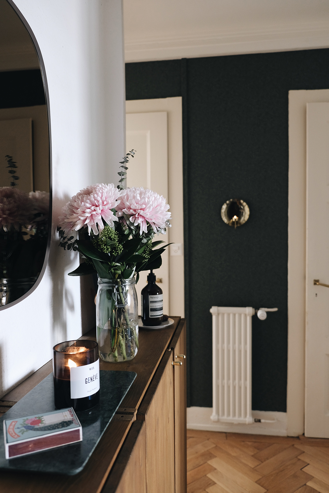 Entryway with brass candle sconce on dark green wallpaper