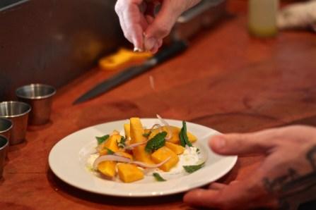 Chef de Cuisine Daniel Ramirez putting the final touches on his mango salad