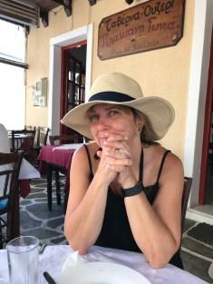 Woman sitting in restaurant in Plaka village, Milos, Greece.
