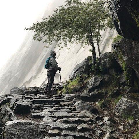 Girl wearing hiking gear walking up moutain.
