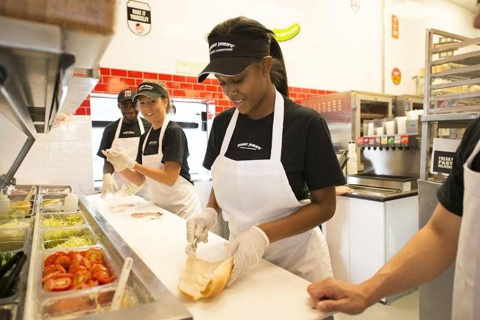 Jimmy John employees having fun making sandwiches