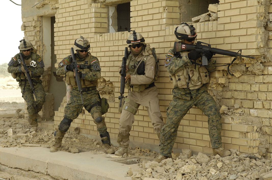 Iraqi soldiers prepare to enter a house in a drill