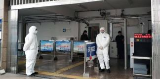People in protective suits at a health checkpoint in Beijing