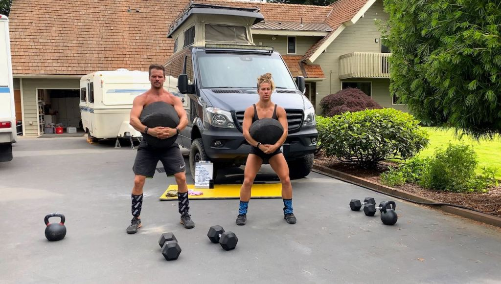 Joe and Emily doing Rogue Strongman Sandbag front squats in the driveway