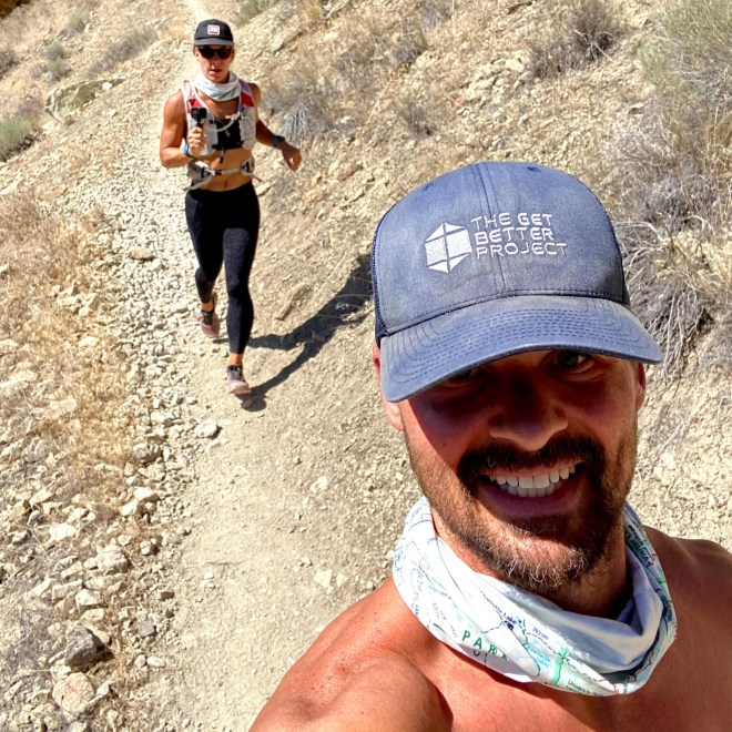 Emily and Joe trail running with Get Better Project hat