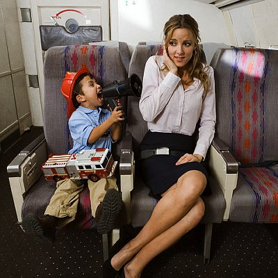 Little Boy Annoying Young Woman Passenger --- Image by © Walter Lockwood/Corbis