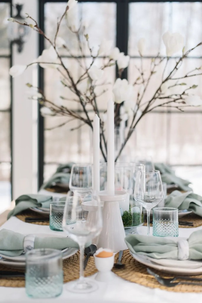 Tapered candles, green water glasses and wine glasses with green linen napkins on a table