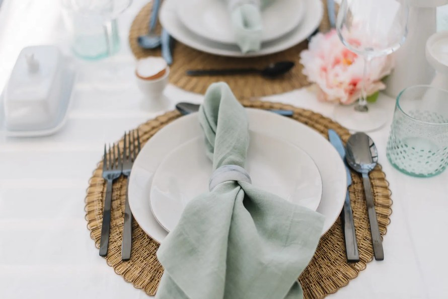 A simple place setting for Easter with linen napkins, black cutlery, and beautiful glassware